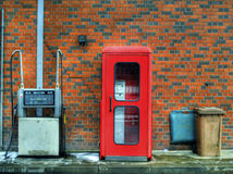 Call booth and filling pump. Telephone and petrol with a brick wall Stock Image