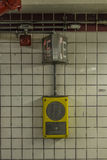Call box on a tiled wall in a subway station Stock Photos