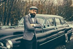 Call boy in vintage auto. Escort man or security guard. Retro collection car and auto repair by mechanic driver. Bearded. Man in car. Travel and business trip stock images