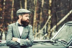 Call boy in vintage auto. Travel and business trip or hitch hiking. Escort man or security guard. Bearded man in car. Retro collection car and auto repair by royalty free stock photography