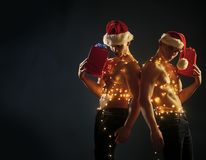 Call boys or athlete men at xmas. Young men in santa costume, present for girls. Twins santa with muscular body in garland. Christmas party and sex games. New royalty free stock photography