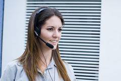 Call center. Pretty profile  woman answering phone Royalty Free Stock Images