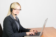 Call Center Agent. Having a telephone call and types on computer Royalty Free Stock Photos