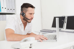 Call center agent on a call at his desk Royalty Free Stock Photography
