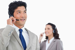 Call center agent with headset and colleague behind him Royalty Free Stock Image