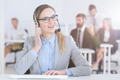 Call center agent at her desk. Professional call center agent working at her desk Royalty Free Stock Photo