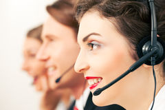 Call center agents. Group of three customer care representatives in a call center with headphones Royalty Free Stock Photography