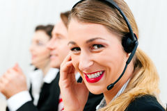 Call center agents. Group of three customer care representatives in a call center with headphones Stock Image