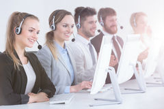 Call center agents in a row. Smiling call center agents sitting in a row and using computers Royalty Free Stock Images