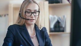 Call-Center-Angestellter bei der Arbeit im Büro Ein junges Mädchen mit dem blonden Haar mit den Gläsern, die an einem Tisch im Bü