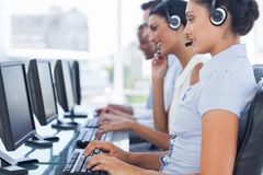 Call-Center-Arbeitskräfte, die in der Linie beim Helfen von Leuten sitzen Stockfoto