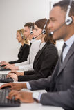 Call center. Attractive positive young colleagues working in call center office. Side view Royalty Free Stock Images