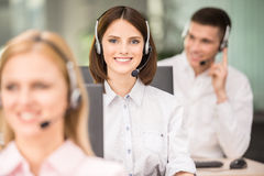Call center. Attractive positive young colleagues working in call center office. Side view stock image