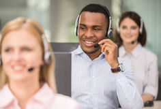 Call center. Attractive positive young colleagues working in call center office. Side view stock photography