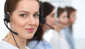 Call center. Beautiful cheerful smiling operator consulting clients with headset. Business concept of customer service.  royalty free stock images