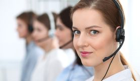 Call center. Beautiful cheerful smiling operator consulting clients with headset. Business concept of customer service.  stock photography