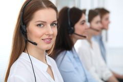 Call center. Beautiful cheerful smiling operator consulting clients with headset. Business concept of customer service.  royalty free stock photo