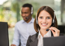 Call center. Beautiful young lady talking on headset at call center office Royalty Free Stock Photos
