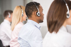 Call center. Call centre workers working in line with their headsets. Back view Royalty Free Stock Photos