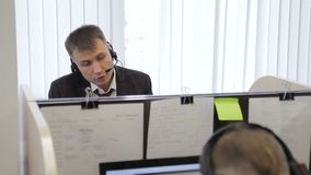 Call center employee is talking while sitting at workplace in company.