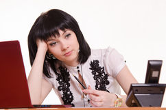 Call-center employee wondered front of monitor, leaned her head on Stock Images