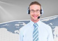 Call-Center-Exekutive mit Kopfhörer lächelnd mit Weltkarte im Hintergrund Stockfotografie