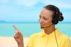 Call center femminile allegra con la cuffia avricolare sui precedenti del cielo Immagine Stock Libera da Diritti