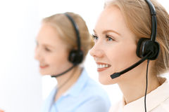 Call center. Focus on beautiful blonde woman in headset Royalty Free Stock Photos