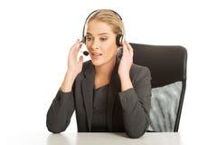 Call-Center-Frau, die am Schreibtisch sitzt Lizenzfreie Stockbilder