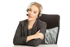 Call-Center-Frau, die am Schreibtisch sitzt Stockbilder