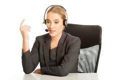 Call-Center-Frau, die am Schreibtisch sitzt Lizenzfreie Stockfotografie