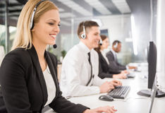 Call center. Group of agents sitting in line in a bright call centre Stock Photos
