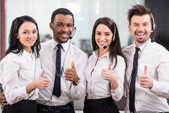 Call center. Group of happy, cheerful call center workers are smiling and looking at the camera Royalty Free Stock Photography