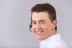 Call center male operator isolated on white. Closeup portrait of young man with headset isolated on grey background stock photo