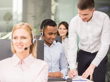 Call center. Manager explaining something to his employee in a call centre Royalty Free Stock Photo