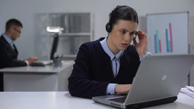 Call center manager in headset checking data on laptop, customer support stock video