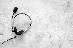 Call center manager`s accessories. Headphones on gery background top view copyspace Stock Image