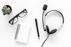 Call center manager`s workplace. Headphones and notebook on white background top view Stock Images
