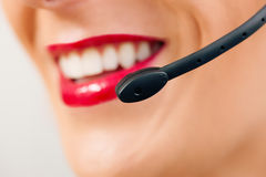 Call center operatator. Portrait of a friendly female call center operator (only parts of face) rendering customer service Royalty Free Stock Image