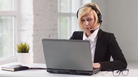 Call Center Operator. Working on customers help line, blonde woman dressed in black jacket and white shirt working on laptop via headset in white office against stock video footage