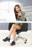 Call center operator in comfortable shoes. Funny portrait of call center operator girl working at desk, sitting in smart top but in comfortable shoes under table stock photography
