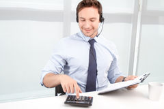 Call center operator counting on calculator Royalty Free Stock Image