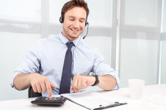 Call center operator counting on calculator Royalty Free Stock Photography
