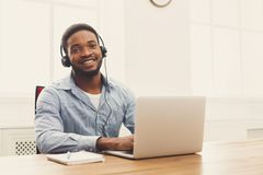 Call center operator man with headset working. Call center operator with headset. African-american man working in support service or hotline in office, copy Royalty Free Stock Photos