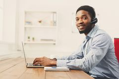 Call center operator man with headset working. Call center operator with headset. African-american man working in support service or hotline in office, copy Royalty Free Stock Photography