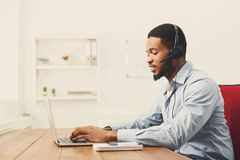 Call center operator man with headset working. Call center operator with headset. African-american man working in support service or hotline in office, copy Royalty Free Stock Photo