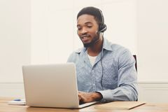 Call center operator man with headset working. Call center operator with headset. African-american man working in support service or hotline in office, copy Stock Photo