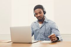 Call center operator man with headset working. Call center operator with headset. African-american man working in support service or hotline in office, copy Stock Image