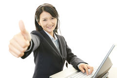 Call center operator showing thumbs up sign Stock Photo
