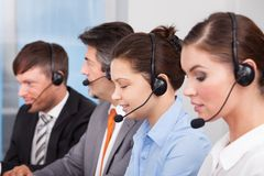 Call center operator. Sitting in row working at office Royalty Free Stock Photo